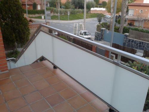 Una solución nítida y armoniosa con el entorno y su disposición, que preserva la intimidad: barandilla de aluminio y vidrio opaco para terraza y escalera.