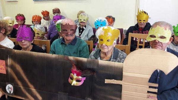 Un nutrido grupo de nuestros residentes con máscaras celebrando el Carnaval en la residencia geriátrica El Recer de Castelldefels