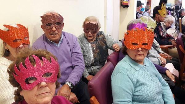 Residentes y familares con máscaras durante la celebración de la fiesta de Carnaval 2017 en la residencia geriátrica El Recer de Castelldefels