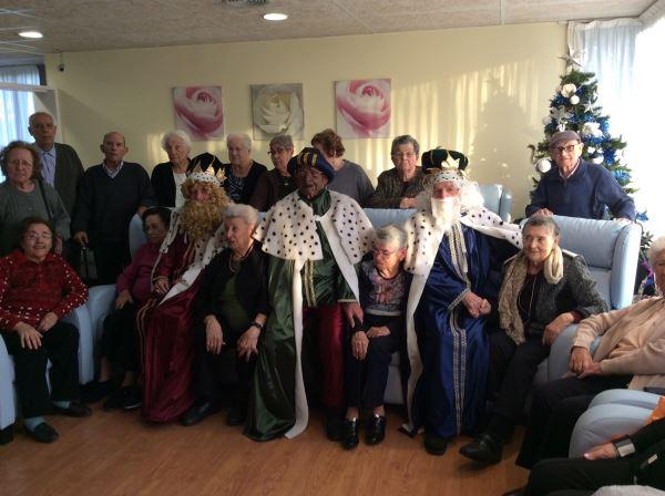 Los Reyes Magos posan con nuestros residentes antes de degustar la chocolatada y los melindres en uno de los salones del centro geriátrico El Recer de Castelldefels