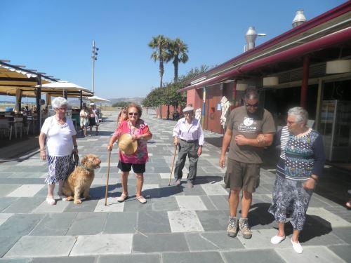 Paseo de los residentes del geriátrico El Recer de Castelldefels por el paseo marítimo con el personal del centro, los perros y los voluntarios de Trifolium