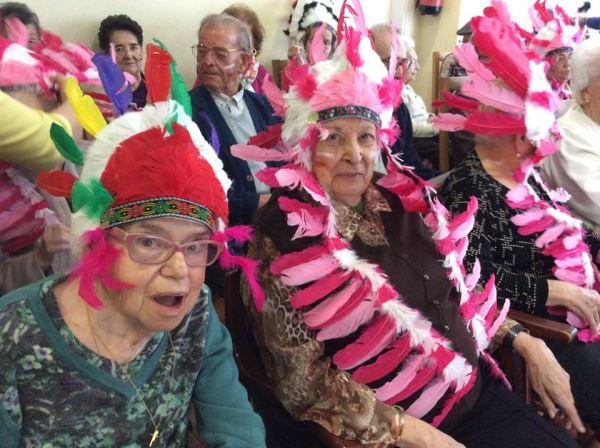 Residentes y familiares ataviados con plumajes indios en la fiesta de disfraces del carnaval 2016 celebrada en la residencia geriátrica El Recer de Castelldefels