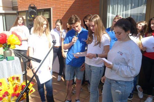 Alumnos del colegio Bon Soleil recitan poemas en los jardines de la residencia geriátrica El Recer de Castelldefels durante la celebración de la Diada de Sant Jordi 2015