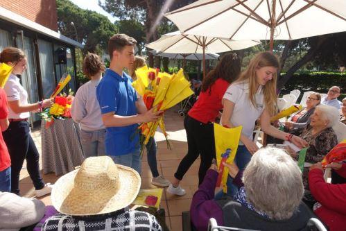 Alumnos del colegio Bon Soleil reparten rosas, y puntos de libro entre los residentes del centro El Recer de Castelldefels durante la celebración de la Diada de Sant Jordi 2015