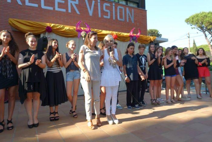 Katy Estarás (con el micrófono), directora del centro Bon Soleil, y Anna Gordillo, directora de la Residencia El Recer en el acto de celebración de #SanJuan2015, rodeadas de los alumnos del colegio