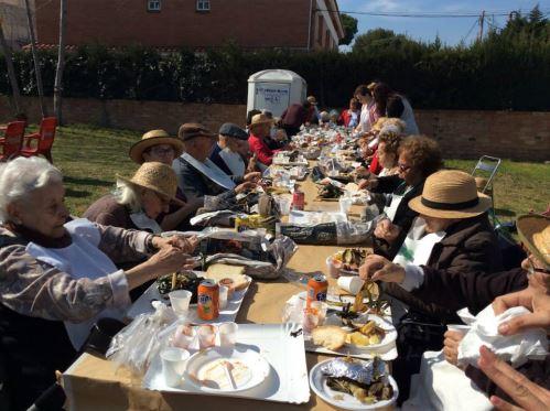 Residentes del centro geriátrico El Recer de Castelldefels en la calçotada de la asociación del Barrio de Les Lluminetes