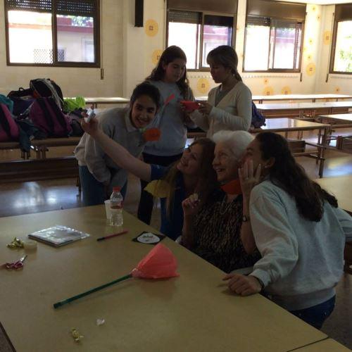 Residente del centro geriátrico El Recer de Castelldefels con alumnas del Colegio Bon Soleil tras el taller de manualidades dedicado a preparar la Diada de Sant Jordi