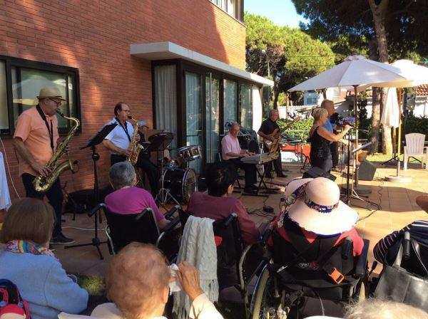 Los residentes y sus allegados disfrutando de la música del grupo Castell Band en los jardines del centro geriátrico El Recer de Castelldefels