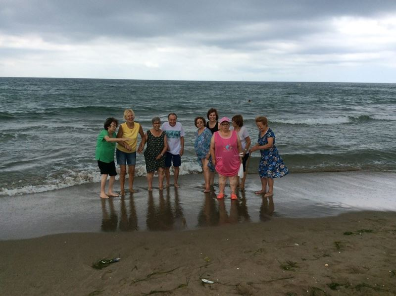 El grupo de residentes de El Recer probando el agua de la playa de Castelldefels