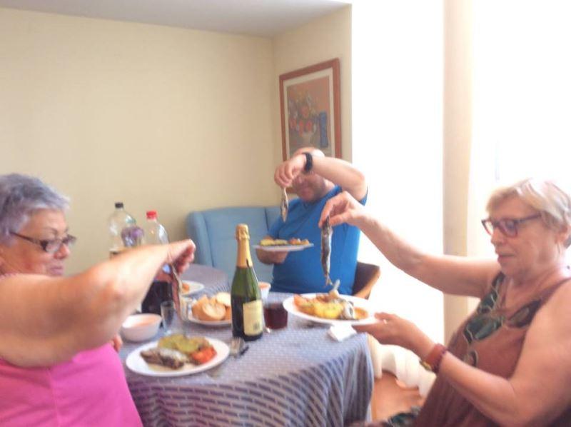 Residente y su familia en el centro El Recer de Castelldefels degustando las sardinas y el acompañamiento en un día festivo y playero
