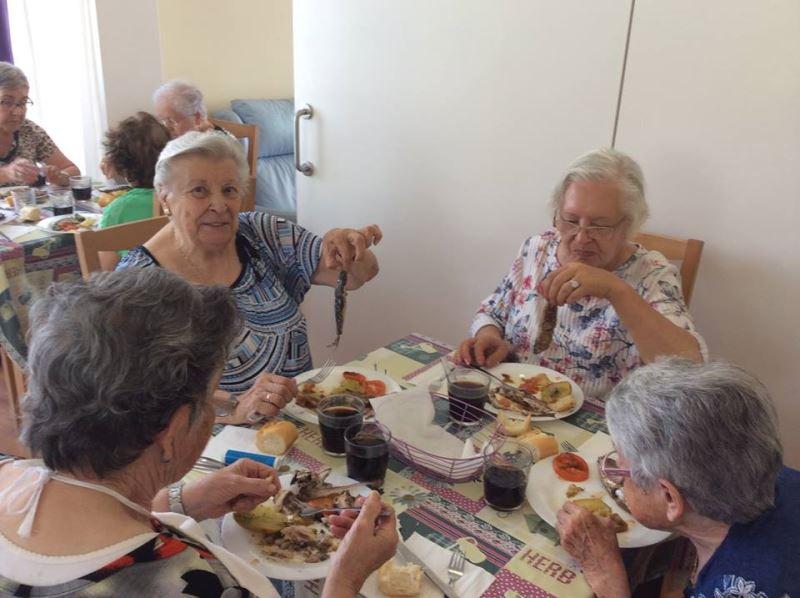 Residentes de El Recer de Castelldefels disfrutando de las fresquísimas sardinas en el Salón Azul del centro geriátrico
