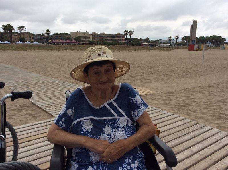 La señora Pepita Pedrol en una de las pasarelas de madera que sirven de acceso a la orilla del arenal de Castelldefels