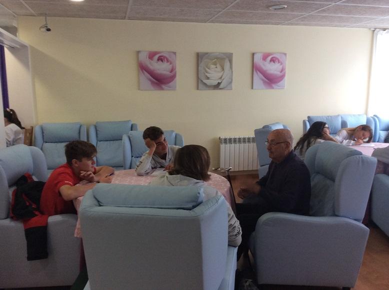 Alumnos del colegio Bon Soleil conversan con nuestro residente en uno de los salones del centro El Recer de Castelldefels