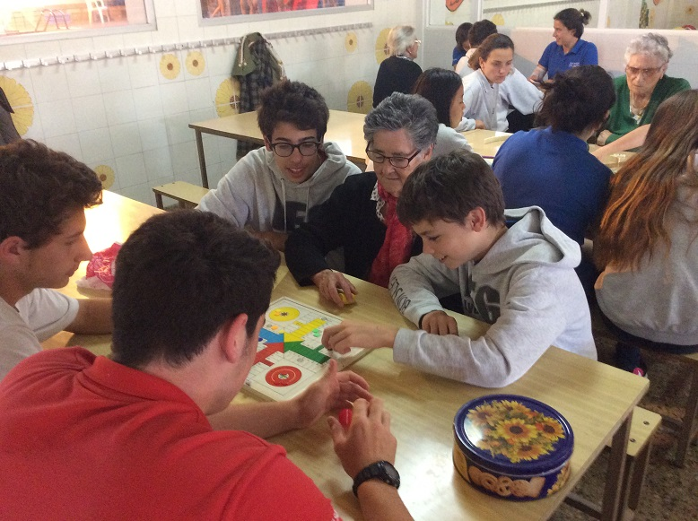 Alumnos del Liceo Francés Bon Soleil y residentes del centro El Recer de Castelldefels practicando con los juegos de mesa durante una de las sesiones sobre historias de vida laboral