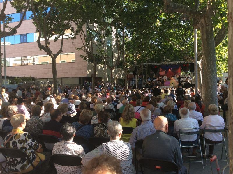 La Plaza de la Iglesia de Castelldefels abarrotada de público en el concierto de la Orquesta Internacional Costa Brava, evento al que acudieron los mayores de la residencia geriátrica El Recer