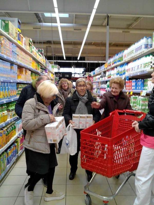Un grupo de residentes del centro El Recer en un híper de Castelldefels efectuando la compra solidaria para el Banco de Alimentos