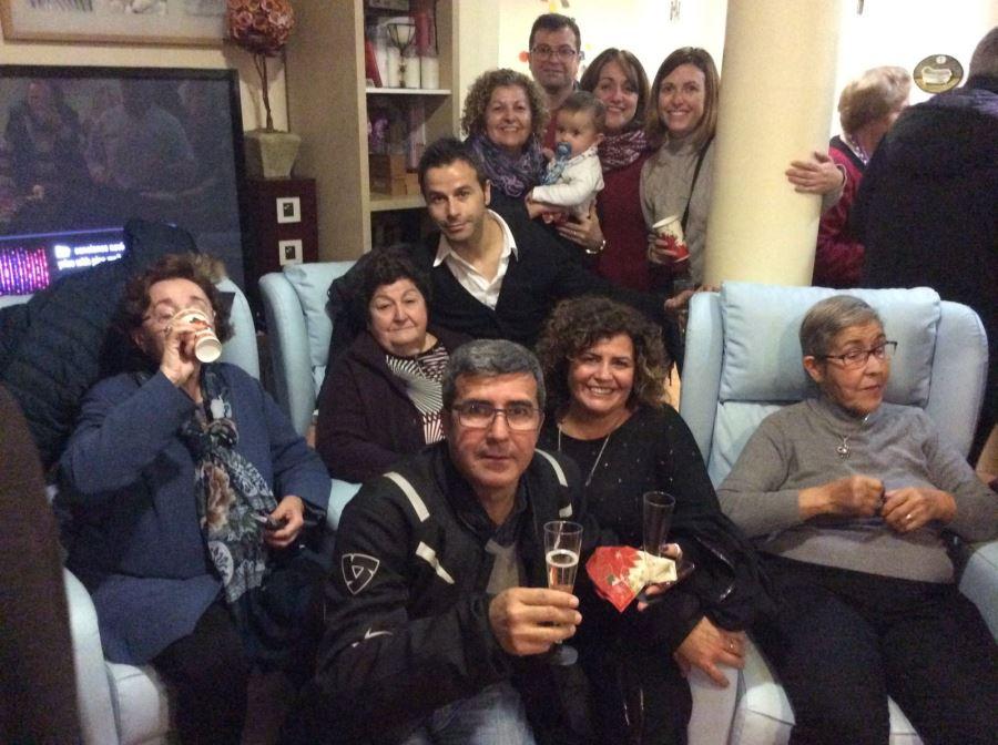 Sentadas en los sofás azules, de izquierda a derecha, las señoras Josefina Cañadillas, Seve Peralta y Nicolasa García rodeadas por los familiares de la segunda durante la celebración de la Navidad 2018