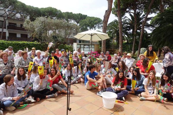 Nuestros residentes con los alumnos y alumnas del colegio Bon Soleil en los jardines de la residencia geriátrica El Recer de Castelldefels