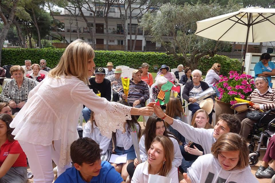 Alumnos y alumnas del colegio Bon Soleil recibiendo sus obsequios de manos de Anna Gordillo, directora de la residencia geriátrica El Recer de Castelldefels