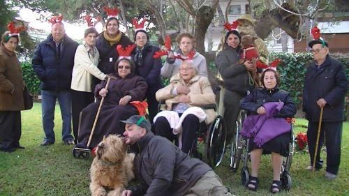 Grupo de residentes y personal, junto a la mascota Balu, en los jardines de la residencia El Recer de Castelldefels, celebrando la Navidad (2014)