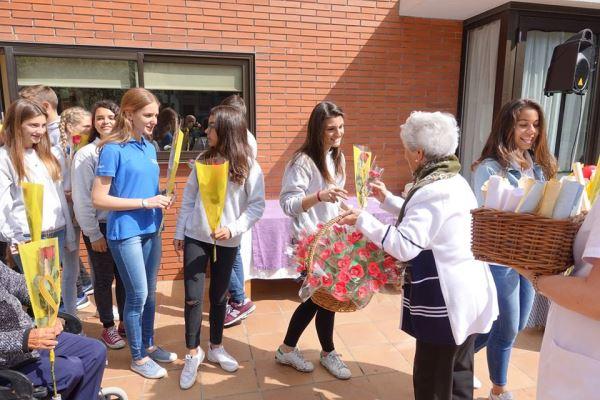 Reparto de las rosas de Goma Eva elaboradas en el taller de terapia ocupacional por los residentes del centro geriátrico El Recer de Castelldefels entre los alumnos del colegio Bon Soleil durante la celebración de la Diada de Sant Jordi 2016