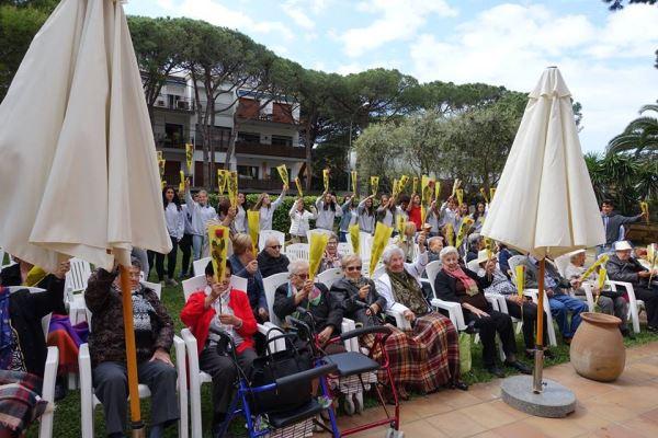 ¡Rosas en alto, esto es Sant Jordi 2016!: impresionante foto de grupo de los jóvenes del colegio Bon Soleil y los residentes y familiares en la celebración de la Diada en el jardín del centro geriátrico El Recer de Castelldefels